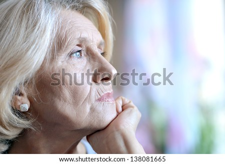 close-up portrait of an old European woman thinking about something - stock photo