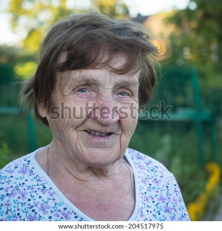 Close-up portrait of an old woman, outdoors. - stock photo