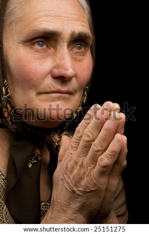 Close up portrait of an old woman praying - stock photo