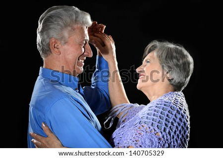 close-up portrait of an older couple on a black background - stock photo