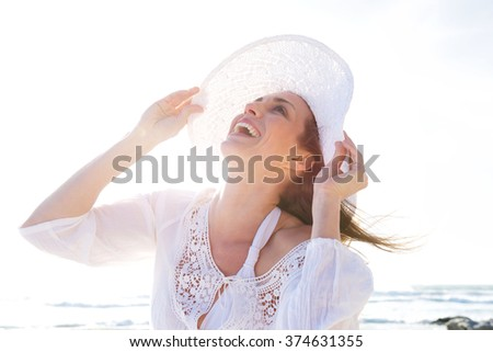 Close up portrait of an older woman laughing with hat at the beach - stock photo