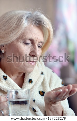close-up portrait of an older woman taking a  medicine - stock photo
