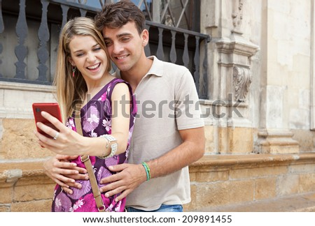Close up portrait of an romantic young couple relaxing taking a selfie picture of themselves with a smartphone visiting a destination city on holiday, together outdoors. Technology lifestyle. - stock photo