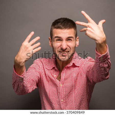 Close-up portrait of angry upset young man with his hands in air. Man with serious glance isolated over grey background. - stock photo