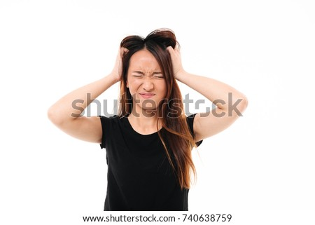 Close-up portrait of annoyed asian woman with closed eyes holding her head, isolated over white background