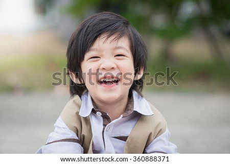 Close up portrait of asian boy laughing - stock photo