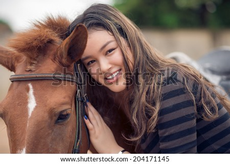 Close-up portrait of Asian girl hugging her bay pony
