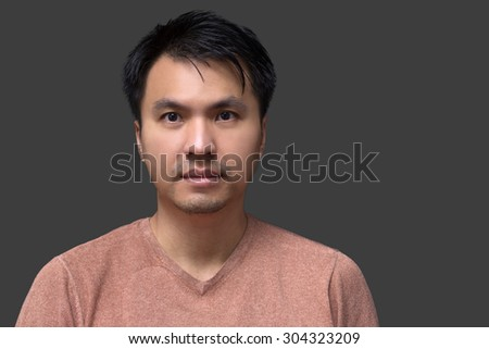 Close up portrait of asian handsome young man in brown t-shirt on dark gray background - stock photo