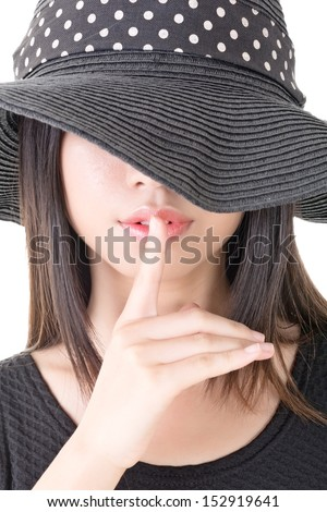 Close-up portrait of asian woman saying hush be quiet. Half covered face by black hat. Isolated on the white background. - stock photo