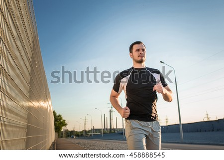 Close-up portrait of athletic man running - stock photo