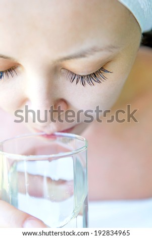 Close-up portrait of attractive asian woman with towel drinking water - stock photo