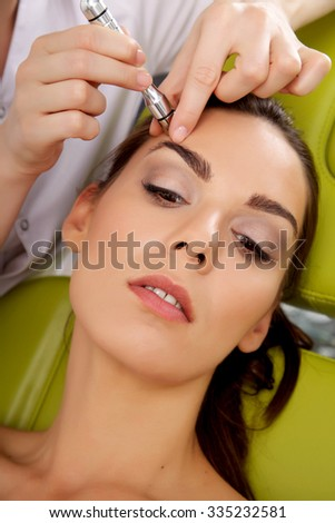 Close up portrait of attractive beautiful young adult brunette woman having a stimulating facial treatment from a therapist on the table in professional clinic spa
