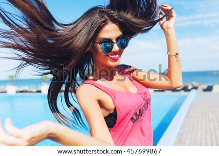 Close-up portrait of attractive brunette girl with long hair  jumping to the camera near pool. She wears pink T-shirt with shorts and sunglasses. She looks very happy.