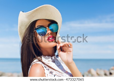 Close-up portrait of attractive brunette girl with long hair standing on the beach near sea. She wears hat, sunglasses and white shirt. She is looking to the camera.