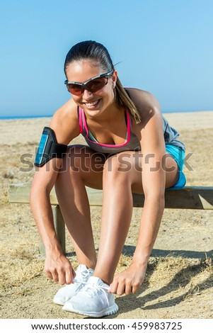 Close up portrait of attractive female runner getting ready to run along beach front.