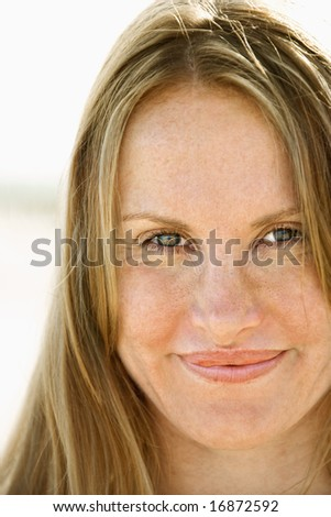 Close up portrait of attractive redheaded woman looking at viewer. - stock photo
