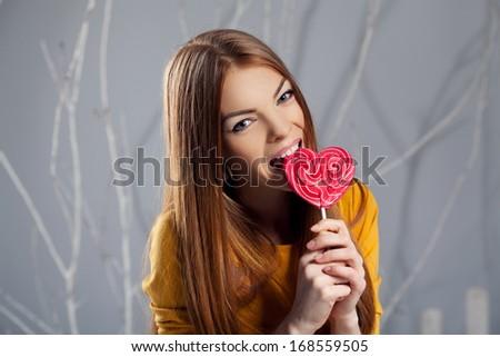close-up portrait of attractive woman bite heart caramel in winter studio interior - stock photo