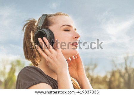 Close up portrait of attractive woman enjoying music on headphones and resting in the nature - stock photo