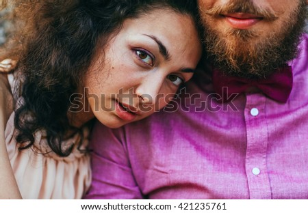 Close up portrait of attractive young couple in outdoor park near old castle. Man with beard, woman with curly hair. - stock photo