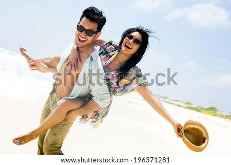 Close up portrait of attractive young couple piggybacking at the beach - stock photo