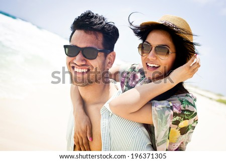 Close up portrait of attractive young couple piggybacking at the beach - soft vintage colors - stock photo