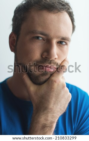 Close-up portrait of attractive young man holding chin. Man standing on gray background with copy space - stock photo