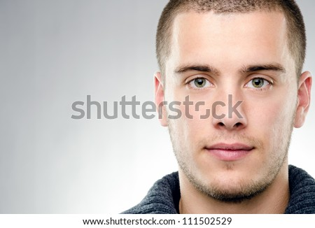 Close-up portrait of attractive young man on gray background with copy space - stock photo