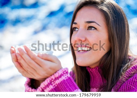 Close up portrait of attractive young woman holding snowflakes in hands outdoors. - stock photo