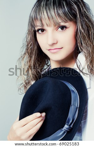 Close up portrait of attractive young woman in a hat on a light background - stock photo