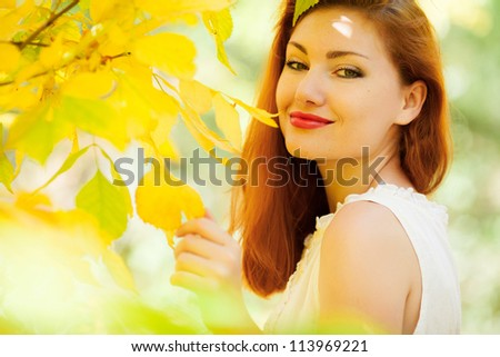 close up portrait of autumn woman with yellow leaves - stock photo