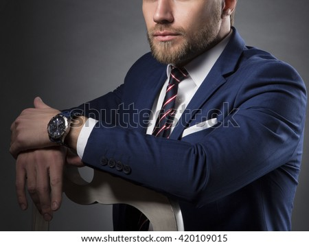 Close-up portrait of bearded caucasian man sitting on wooden chair. Perfect skin. Wearing blue suit and watch. Studio portrait on gradient black to grey background. Toned - stock photo