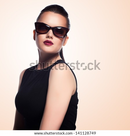close-up portrait of beautiful and fashion girl in sunglasses, studio shot. Professional makeup and hairstyle