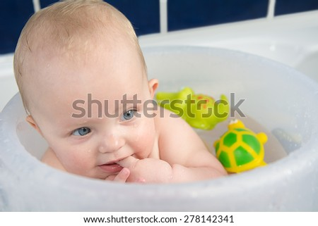 Close up portrait of beautiful baby having  bath and holding her finger in mouth - stock photo