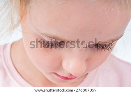 Close-up portrait of beautiful blonde little girl with long eyelashes - stock photo