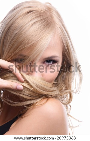 close-up portrait of beautiful blonde model looking shy and hiding her smile in a strand of hair - stock photo