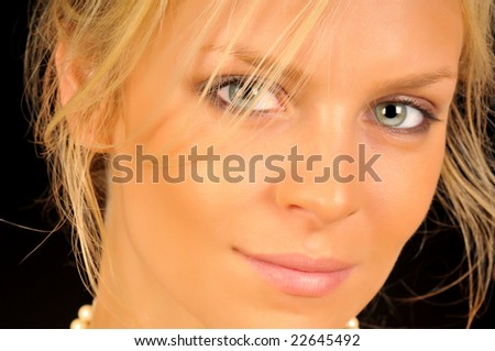 Close up portrait of beautiful blonde woman isolated on black background.