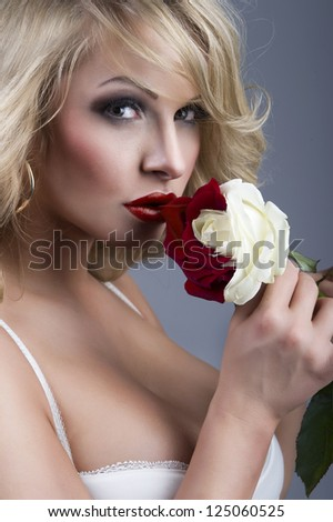close-up portrait of beautiful blonde woman with red - white ros - stock photo
