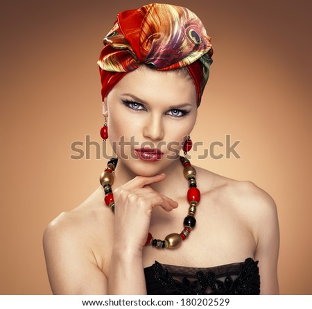 Close-up portrait of beautiful blue eyed woman with ethnic hairstyle wearing nice jewelery. African styled model with red silk turban.