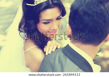 close up portrait of beautiful bride looking at her groom shoulder - stock photo