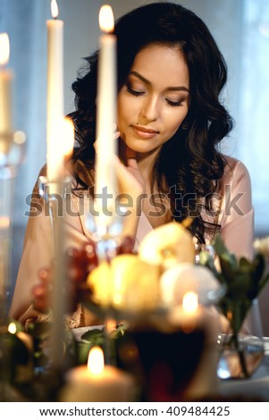 Close-up portrait of beautiful brunette bride before wedding, sitting by a table with decor and candles