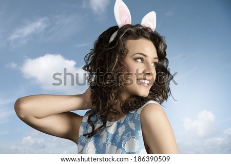 close-up portrait of beautiful brunette girl with easter funny style, pink bunny ears and lovely spring dress  - stock photo