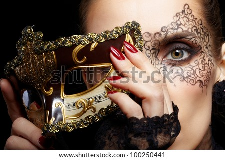 close-up portrait of beautiful brunette woman with facial body art hiding half of her face with carnival venetian mask - stock photo
