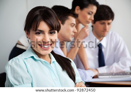 Close-up portrait of beautiful businesswoman smiling while team working in background - stock photo