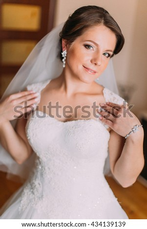 Close up portrait of beautiful caucasian mid adult bride showing her white dress - stock photo