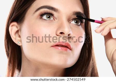 close up portrait of beautiful caucasian model applying mascara - stock photo