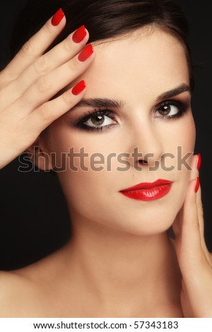 Close-up portrait of beautiful elegant brunette with trendy make-up and red manicure - stock photo