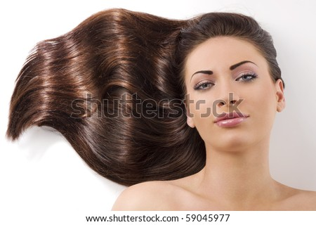 close-up portrait of beautiful female face with long dark waved hairs laying down on the floor - stock photo