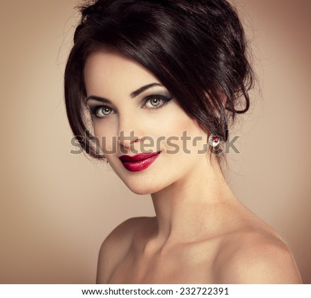 Close-up portrait of beautiful female with evening hairdo and professional makeup. Young pretty Caucasian female fashion model wearing luxury earrings.   - stock photo