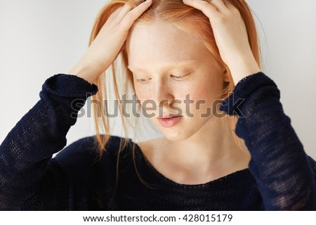 Close up portrait of beautiful freckled teenage girl with mysterious smile, wearing casual black top, looking down touching her ginger hair with dreamy expression. Positive human face expressions - stock photo
