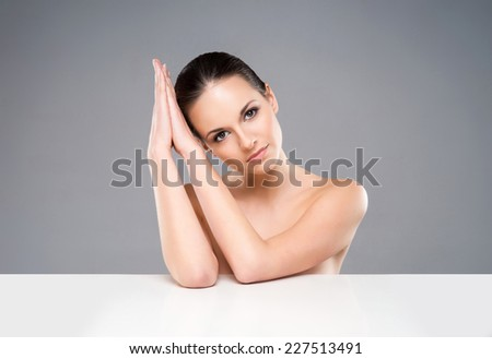 Close-up portrait of beautiful, fresh, healthy and sensual girl over grey background - stock photo